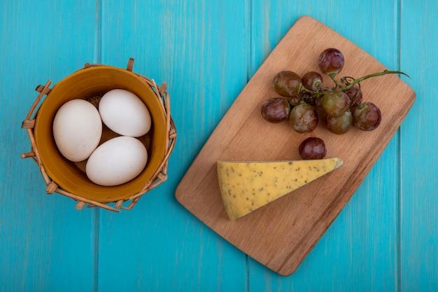 Vista superior de queso con uvas en una tabla y huevos de gallina en una canasta sobre un fondo turquesa