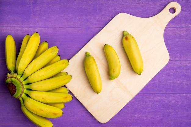 Vista superior del racimo de plátanos en tabla para cortar madera en madera morada