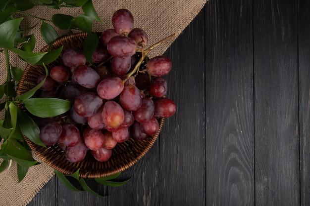 Vista superior de un racimo de uvas frescas dulces en una cesta de mimbre en la mesa de madera con espacio de copia