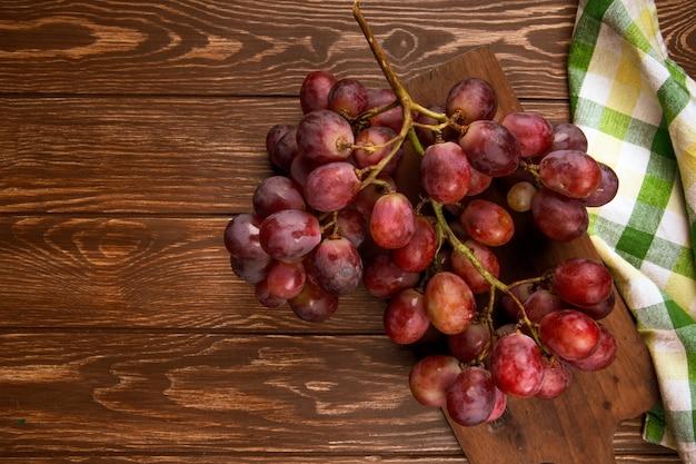 Vista superior de un racimo de uvas frescas en la mesa rústica de madera