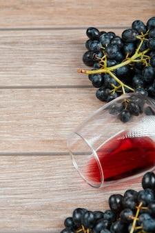 Vista superior de un racimo de uvas negras y una copa de vino en la superficie de madera