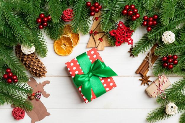 Vista superior de ramas de abeto, regalos y juguetes decorativos festivos en mesa de madera