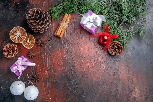 Vista superior de las ramas de los árboles de pino con conos juguetes de árbol de navidad rodajas de limón seco canela anís estrellado en la superficie de color rojo oscuro