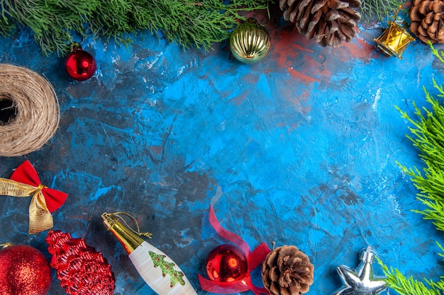 Vista superior de las ramas de los árboles de pino con piñas de hilo de paja adornos colgantes de navidad en la superficie azul-roja