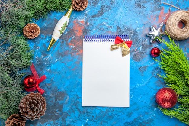 Vista superior de las ramas de los árboles de pino con piñas, un hilo de paja de un cuaderno sobre una superficie azul-roja