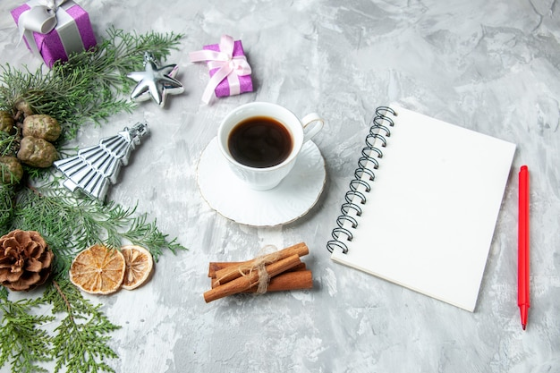 Vista superior de ramas de pino cuaderno lápiz taza de té piñas pequeños regalos en superficie gris