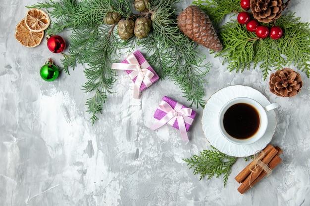 Vista superior ramas de pino pequeños regalos juguetes de árbol de navidad palitos de canela sobre fondo gris
