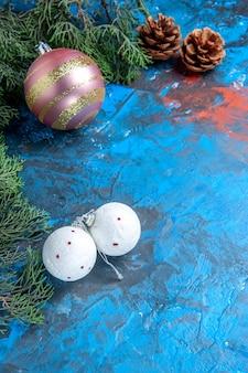 Vista superior de ramas de pino piñas bolas de árbol de navidad en superficie azul-roja