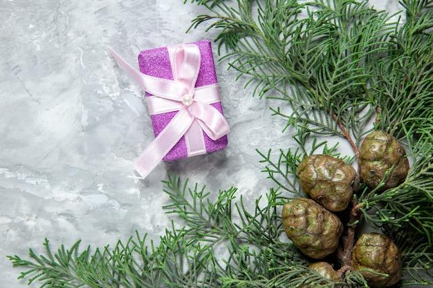 Vista superior de ramas de pino piñas pequeño regalo en superficie gris