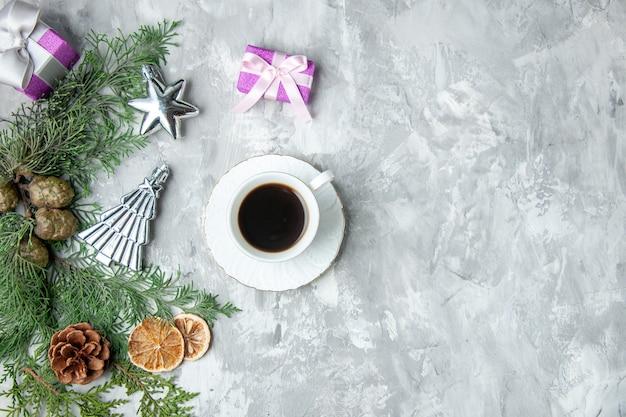 Vista superior ramas de pino taza de té rodajas de limón seco piñas pequeños regalos en superficie gris