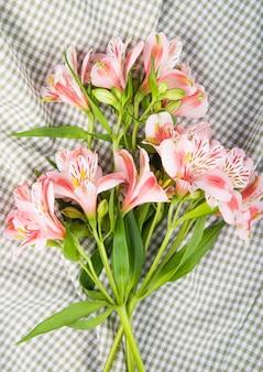 Vista superior de un ramo de flores de alstroemeria de color rosa sobre fondo de tela escocesa