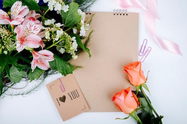 Vista superior de un ramo de flores de color rosa alstroemeria con viburnum floreciente y un cuaderno de bocetos con una postal y rosas de color coral sobre fondo blanco.