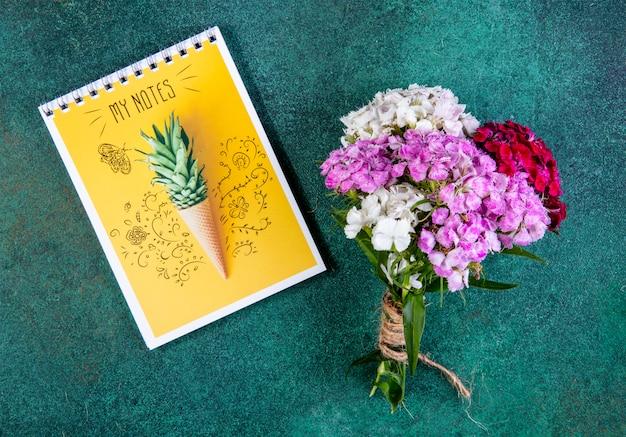 Vista superior ramo de flores de colores con notas amarillas sobre verde