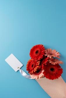 Vista superior del ramo de flores con tarjeta en blanco