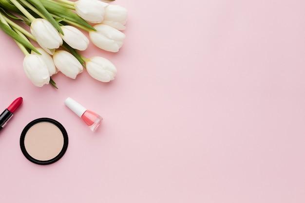 Vista superior ramo de flores de tulipán y maquillaje