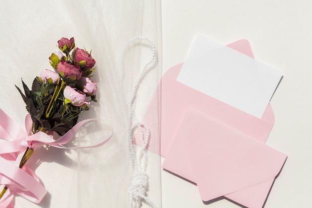 Vista superior ramo de rosas en velo junto a invitaciones de boda