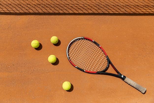 Vista superior de raquetas y pelotas de tenis en la cancha