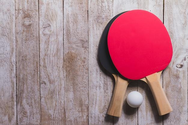 Vista superior de raquetas de ping pong sobre superficie de madera