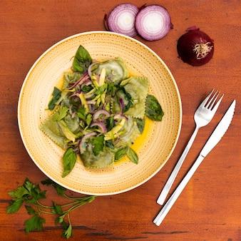 Vista superior de ravioles verdes con cebolla y albahaca deja mesa de madera