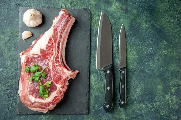 Vista superior rebanada de carne fresca con cuchillos sobre fondo azul oscuro cocina animal comida de vaca carnicero carne color pollo