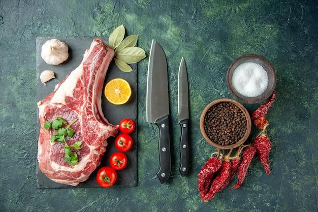 Vista superior de la rebanada de carne fresca en la superficie azul oscuro