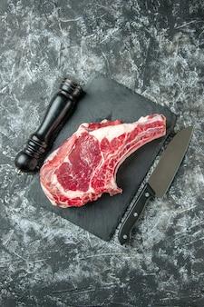 Vista superior de la rebanada de carne fresca en la superficie gris claro
