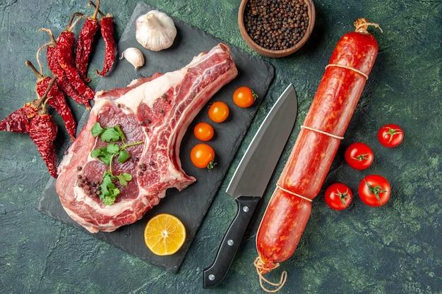 Vista superior de la rebanada de carne fresca con tomates naranjas y salchichas sobre fondo azul oscuro color comida carne cocina animal pollo vaca carnicero