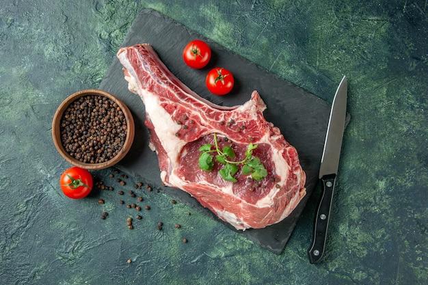 Vista superior de la rebanada de carne fresca con tomates y pimiento sobre un fondo azul oscuro carne de carnicero de color de comida de pollo de vaca animal de cocina