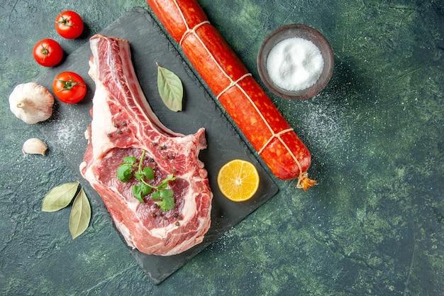 Vista superior de la rebanada de carne fresca con tomates y salchichas sobre fondo azul oscuro cocina animal vaca comida color carnicero carne pollo