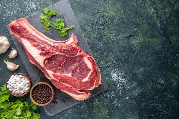 Vista superior rebanada de carne grande carne cruda con pimienta sobre superficie oscura