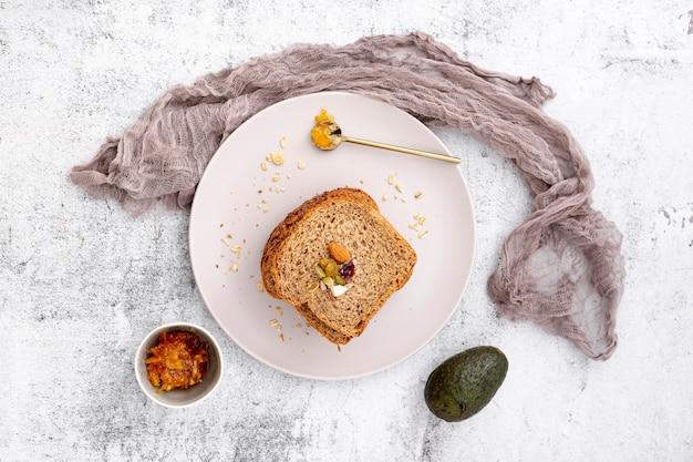Vista superior rebanada de pan con aguacate y tela