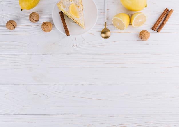 Vista superior de la rebanada de pastel decorado; limón; nueces canela; cuchara sobre fondo de madera blanco