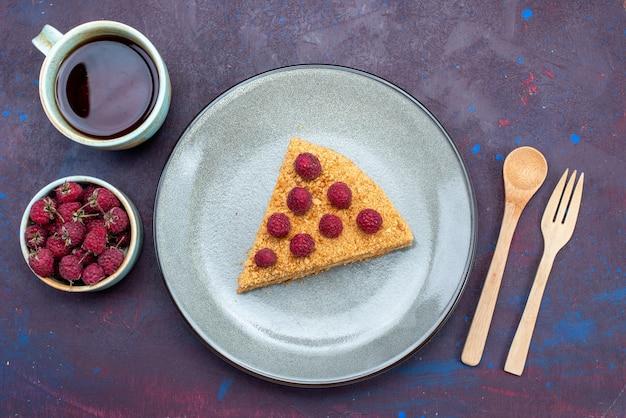 Vista superior de la rebanada de pastel delicioso con frambuesas y té en la superficie oscura