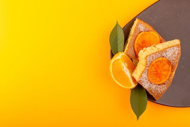 Una vista superior rebanada de pastel de naranja dulce deliciosa pieza sabrosa en el escritorio de madera de color marrón y fondo amarillo galleta de azúcar dulce
