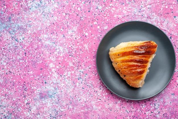 Vista superior de la rebanada de pastelería con relleno verdoso dentro de la placa sobre la superficie rosada