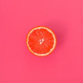 Vista superior de una rebanada de un pomelo sobre fondo brillante en color rosa claro. una imagen saturada de textura cítrica.