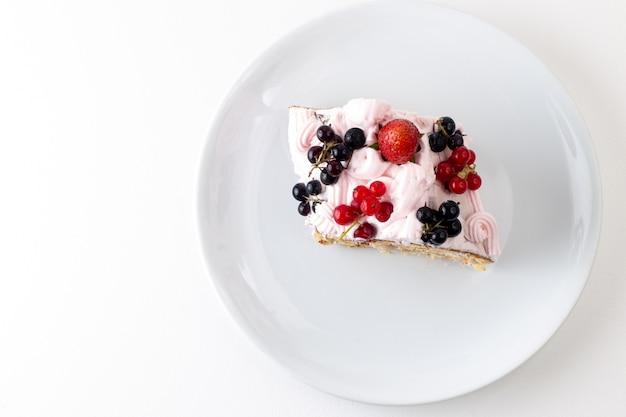 Vista superior de la rebanada de rollo con crema de arándanos y fresa dentro de la placa blanca sobre el fondo blanco pastel de galleta color dulce