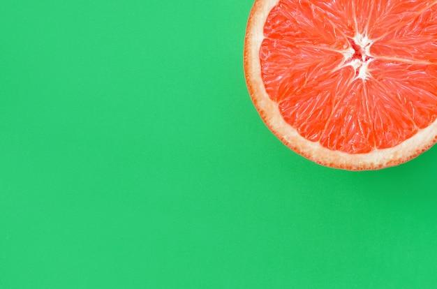 Vista superior de una rebanada de toronja sobre un fondo brillante en color verde