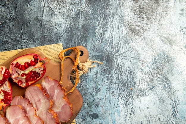 Vista superior rebanadas de carne cortada granada en tabla de cortar sobre superficie gris de periódico