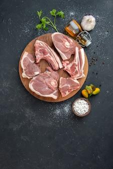 Vista superior rebanadas de carne fresca carne cruda en plato de barbacoa oscuro pimienta comida de cocina ensalada de comida de vaca comida de animal