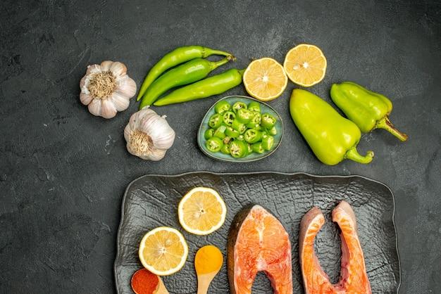 Vista superior de las rebanadas de carne frita con pimientos, ajo y limón sobre fondo oscuro