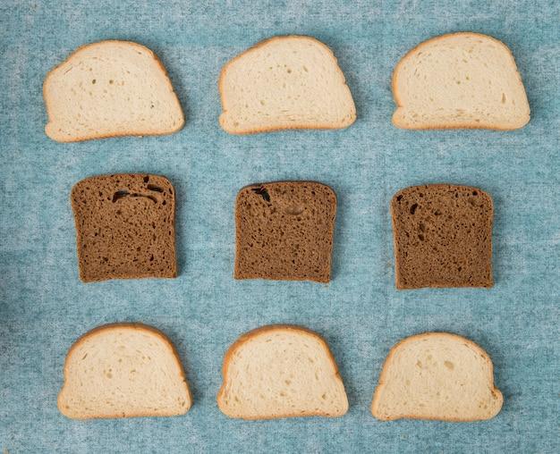 Vista superior de rebanadas de pan blanco y negro sobre fondo azul.