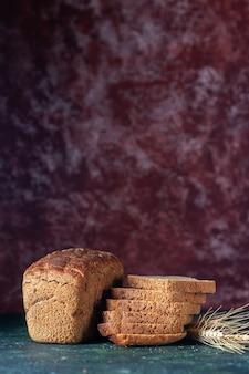 Vista superior de rebanadas de pan negro dietético y picos sobre fondo de colores mezclados granate azul con espacio libre