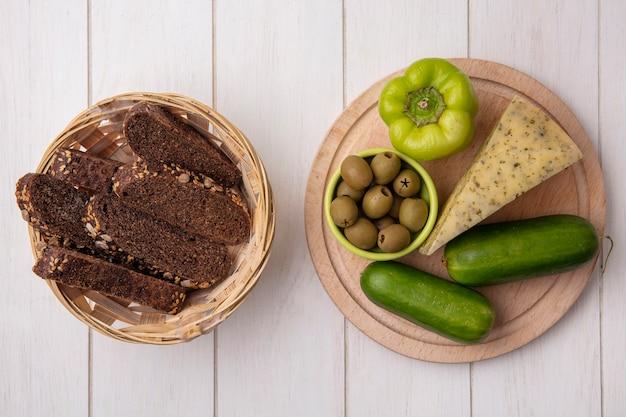 Vista superior de rebanadas de pan negro con queso y pepinos con pimientos en un soporte con aceitunas sobre un fondo blanco.