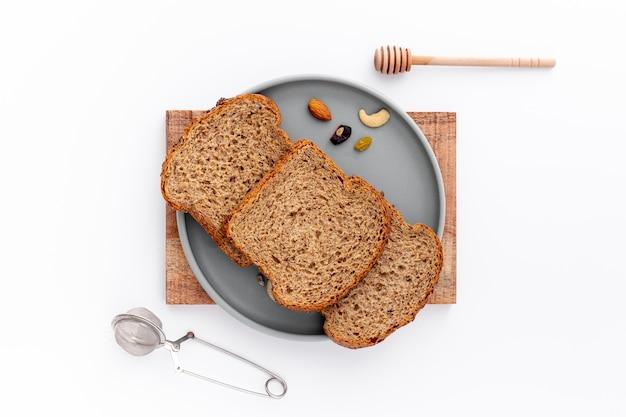 Vista superior rebanadas de pan en placa y fondo blanco.