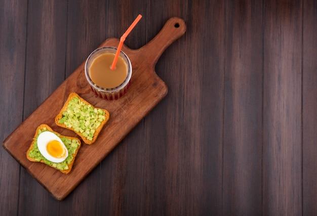 Vista superior de rebanadas de pan tostado con pulpas de aguacate y huevo con jugo en un vaso sobre una tabla de cocina de madera sobre una superficie de madera
