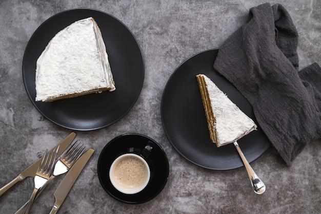 Vista superior rebanadas de pastel con café sobre la mesa
