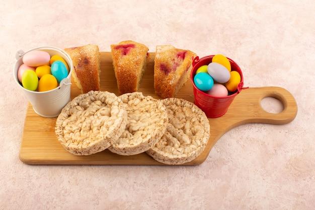 Una vista superior de las rebanadas de pastel de cereza con dulces y galletas en el escritorio rosa pastel de azúcar