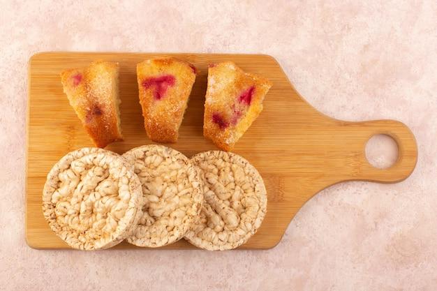Una vista superior de las rebanadas de pastel de cereza con galletas en el escritorio rosa pastel galleta azúcar dulce