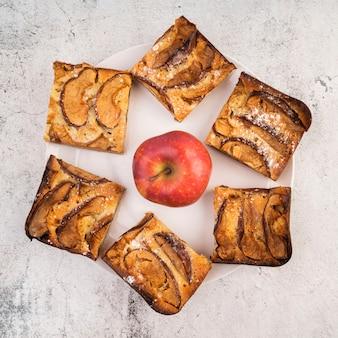 Vista superior rebanadas de pastel y una manzana sobre la mesa